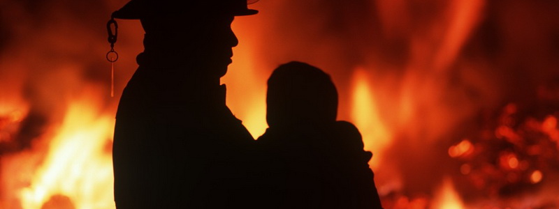 Silhouette of fireman carrying child with burning house beyond, British Columbia, Canada.