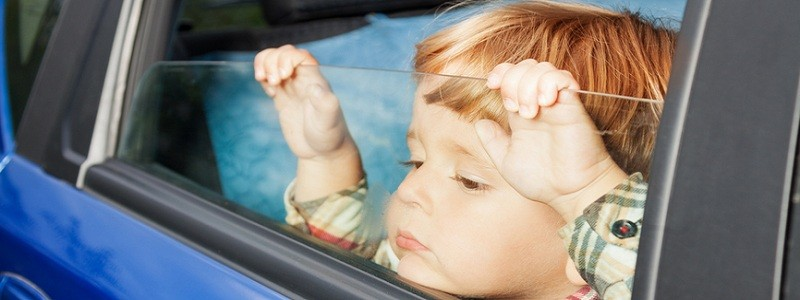 little kid is sitting sad on the back sit and look tired of car trip